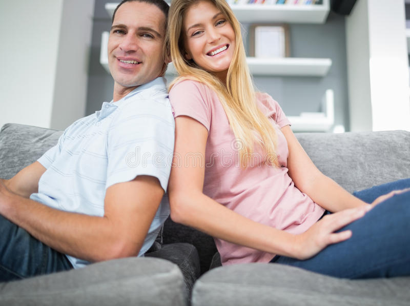 Content Couple Sitting Back To Back On The Couch Together Stock Photo