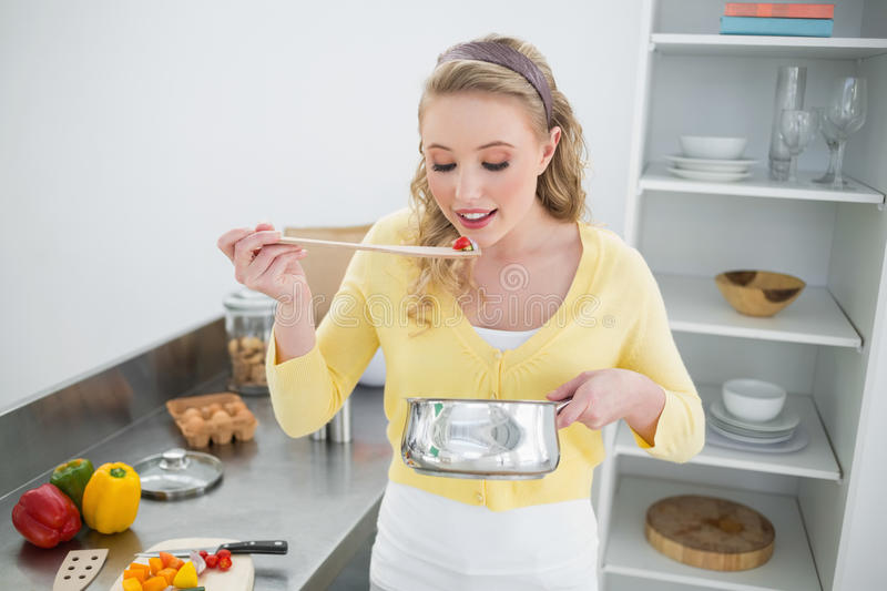 Content cute blonde tasting food from wooden spoon stock photos