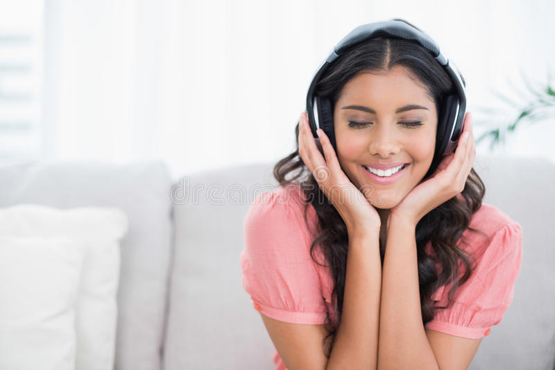 Content cute brunette sitting on couch listening to music with closed eyes stock images