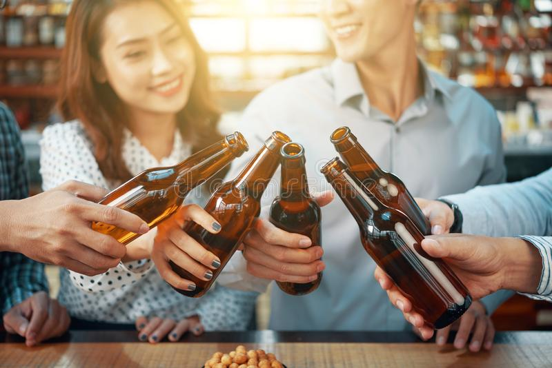 Content friends toasting with beer bottles stock photos