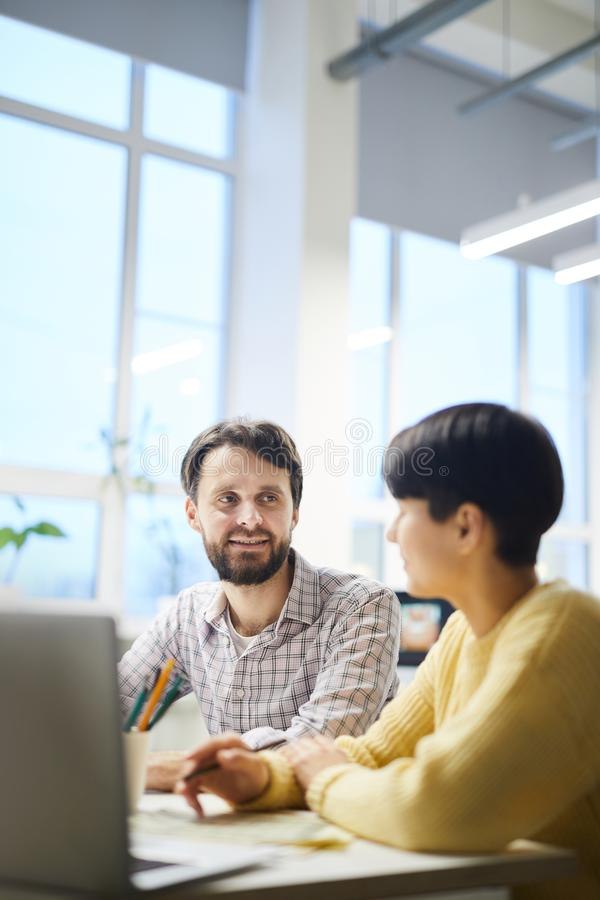 Hipster colleagues discussing ideas in office royalty free stock photo