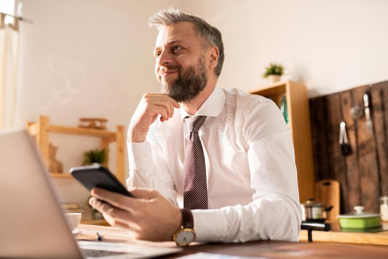 Content inspired businessman reading message at home royalty free stock photo