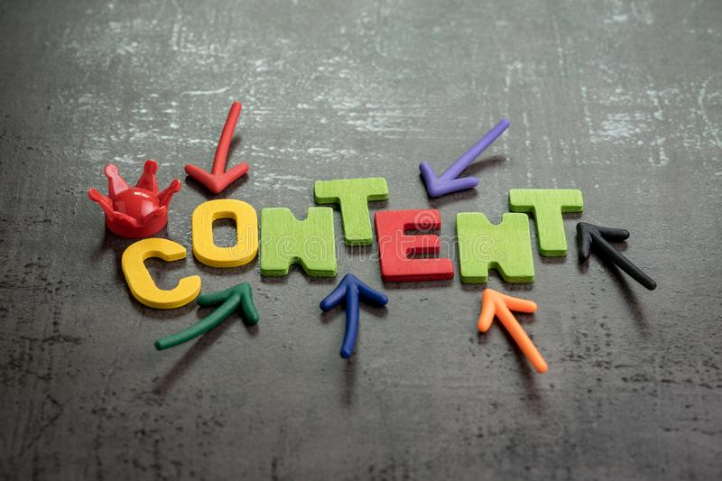 Content is king in brand communication and advertising concept idea, colorful arrows pointing to the word CONTENT at the center. With red crown on black cement royalty free stock photo