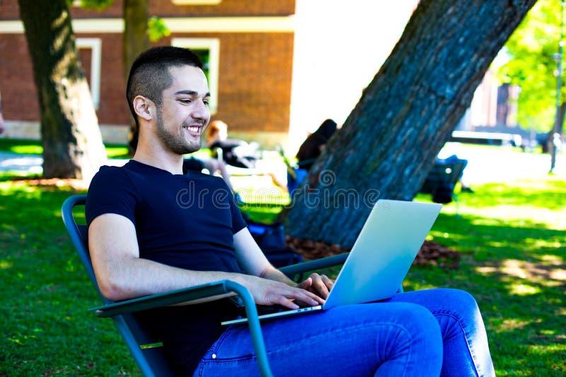Content manager maschio allegro che scrive testo a macchina su netbook durante il tempo di ricreazione all'aperto fotografie stock libere da diritti