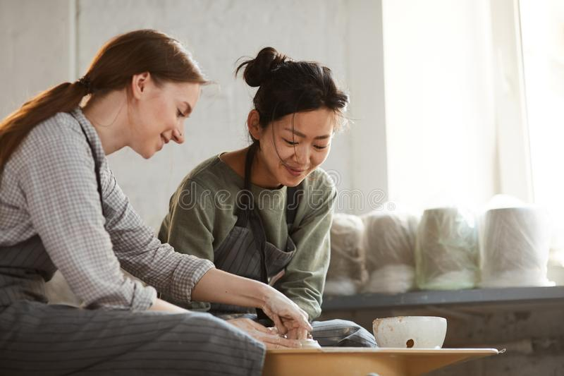 Content multi-ethnic women creating clay pot together royalty free stock images