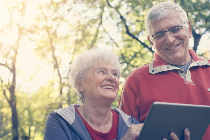 Senior couple standing in park and using iPod. Close up. royalty free stock photos