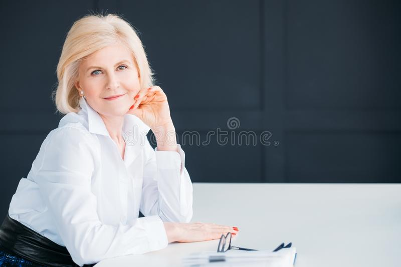 Content senior woman relaxed executive rest time. Content senior woman. Relaxed posture. Corporate executive rest . Aged lady looking at camera satisfied. Copy stock image
