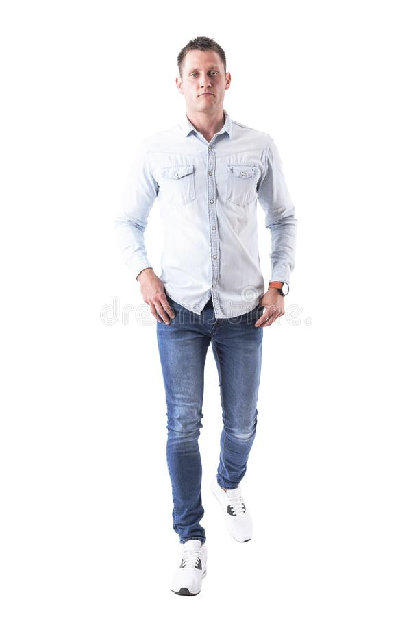 Content serious young successful man walking with hands in pockets looking at camera stock photos