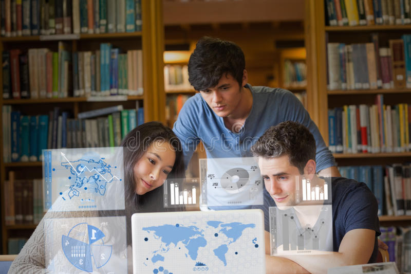 Content students working on digital interface. In university library royalty free stock photography