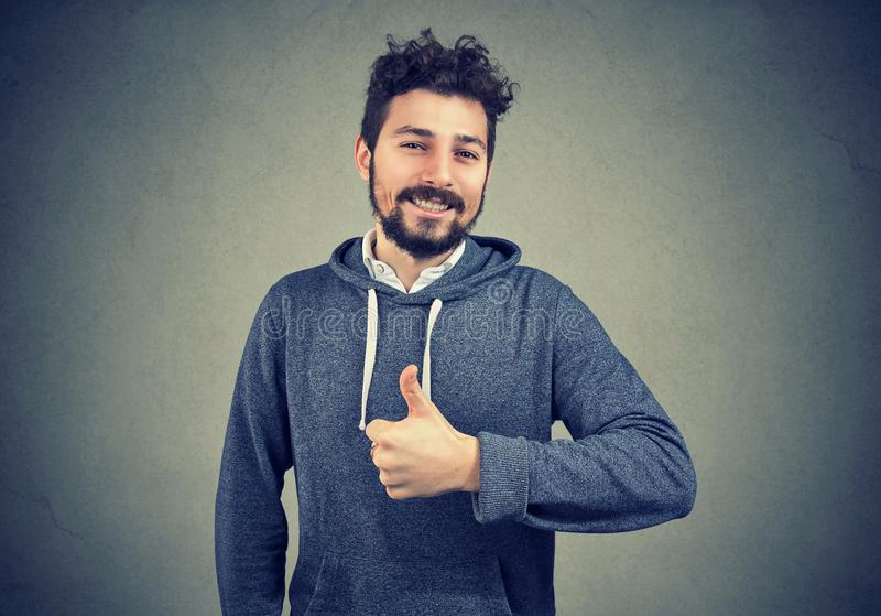 Content successful hipster gesturing on gray stock photo