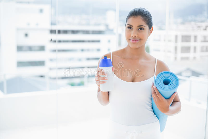 Content toned brunette holding sports bottle and exercise mat royalty free stock image