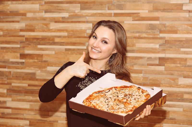 Content woman pointing at pizza royalty free stock images