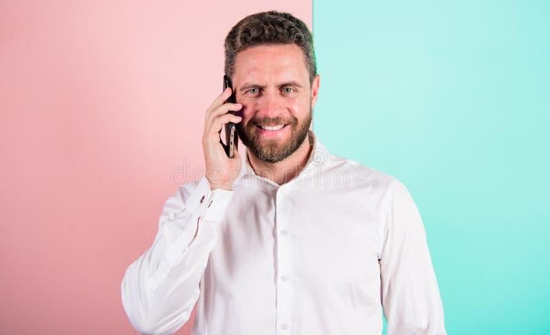 Contente de ouvi-lo Telefone de sorriso farpado da chamada da cara do homem Conversação móvel com amigo Uma comunicação móvel man fotografia de stock
