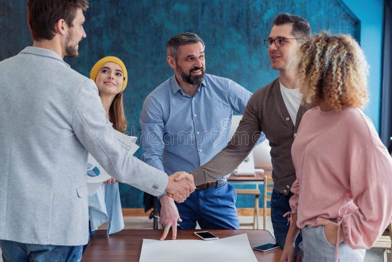 Contente de trabalhar com você! Homens modernos novos no vestuário desportivo esperto que agita as mãos e que sorri ao trabalhar  fotos de stock
