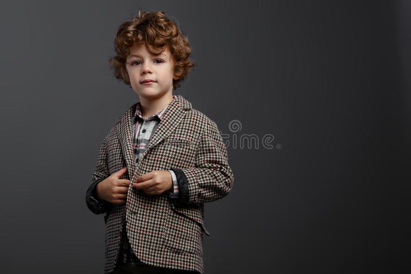 Contented boy cute boy with red curly hair dressed in a elegant suit,  on a grey background, with copy space royalty free stock photo