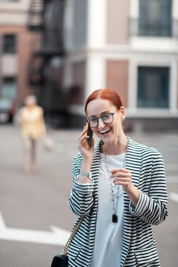 Contented red-haired Caucasian young business lady in eyeglasses stock image