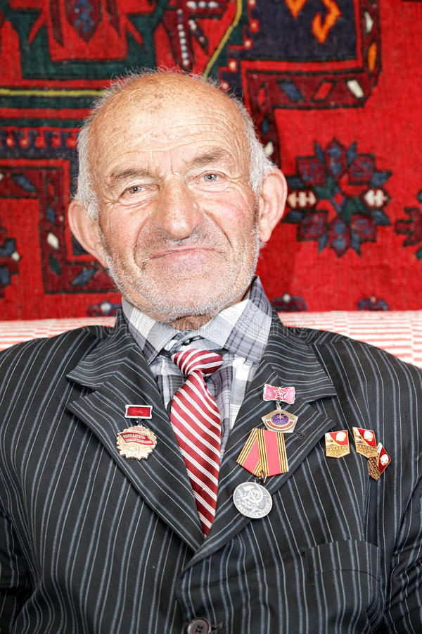 Contented senior man with medals. Portrait of contented senior man with various medals stock image