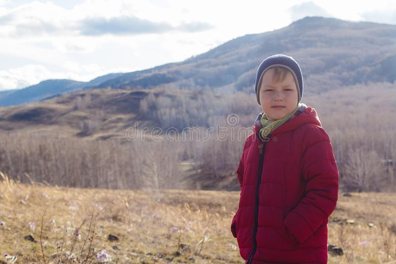 A contented six-year-old boy in a warm red jacket keeps his hands in his pockets outdoors royalty free stock photo