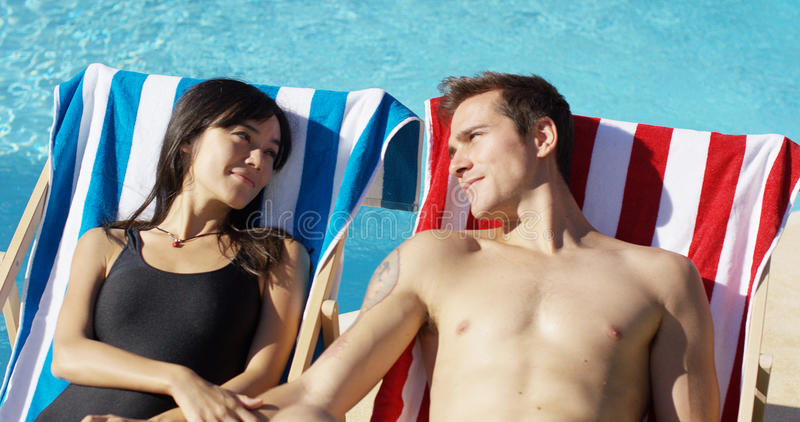 Contented young couple smiling as they sunbathe royalty free stock images