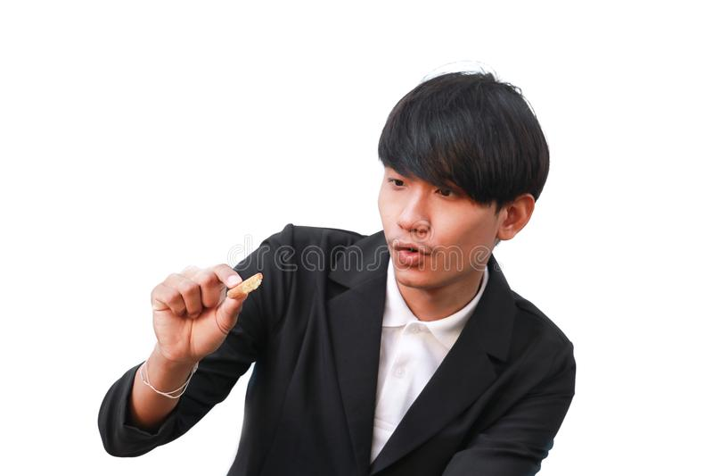 Contentes consideráveis do homem novo comem a cookie partes pequenas no fundo branco imagem de stock