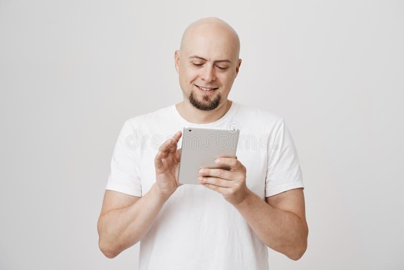 Contento madure al hombre calvo con la barba que hojea con la tableta o la mensajería, colocándose sobre fondo gris acertado imágenes de archivo libres de regalías