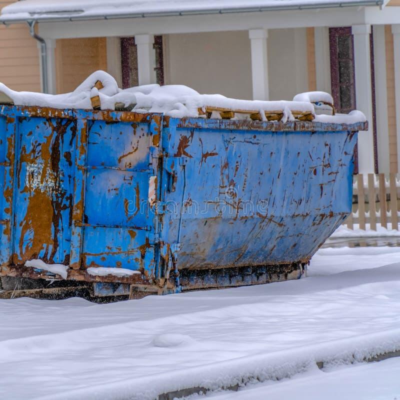 Contentor quadrado na terra coberto de neve contra casas na aurora Utá foto de stock