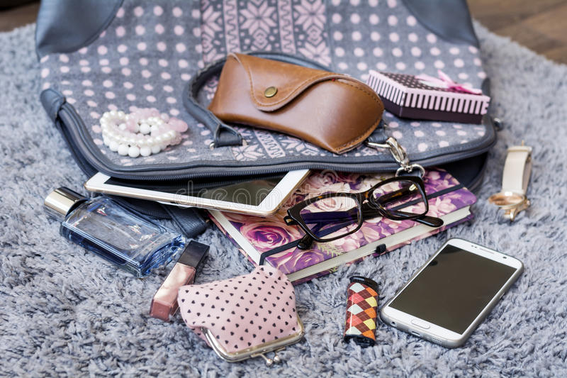 The contents of the female handbag. Phone, tablet ,notebook, lipstick, perfume ,watch,lipstick,eyeglasses royalty free stock images