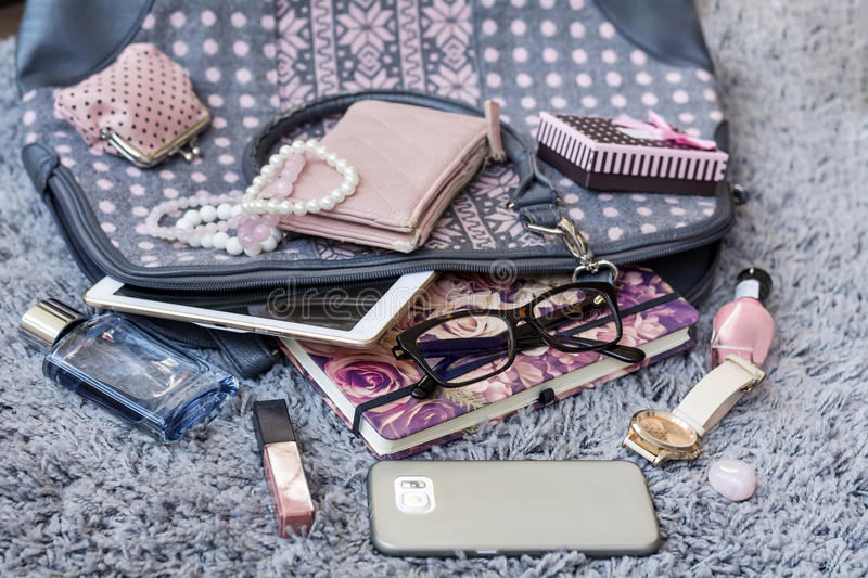 The contents of the female handbag. Phone, tablet ,notebook, lipstick, perfume ,watch,lipstick,eyeglasses royalty free stock image