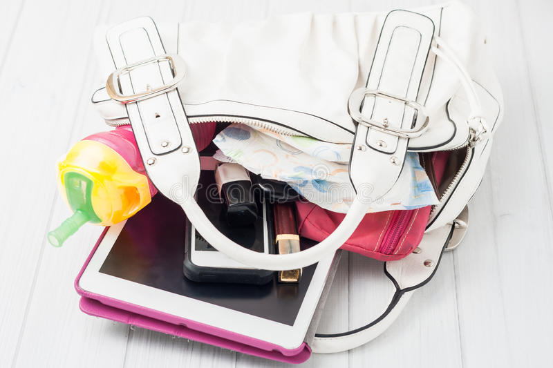 Contents of a woman's bag. Contents of a mother's white shoulder bag on white background royalty free stock photography
