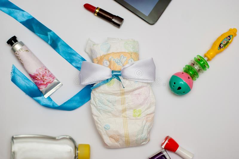 Contents of a woman`s bag on white background. Contents include: tablet, lipstick, hand cream, nail polish, baby oil, toy and a diaper royalty free stock photos