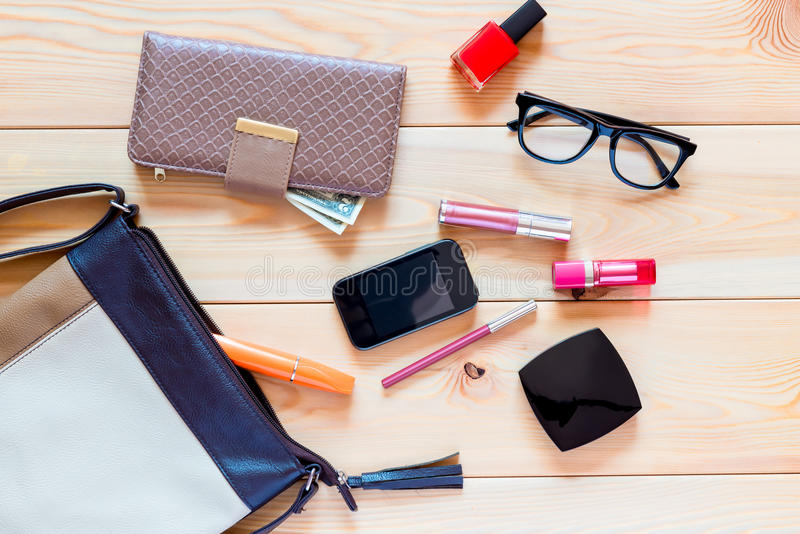 The contents of women's handbags are scattered. On the floor stock photo