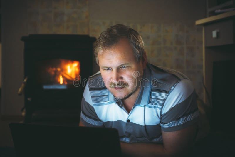 Contenu de observation d'homme sur un ordinateur portable le soir à la maison par la cheminée photo libre de droits