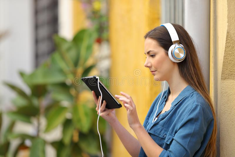 Contenuto d'ascolto e di sorveglianza della ragazza seria della compressa immagine stock