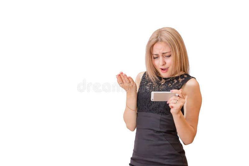 Contenuto di sorveglianza turbato di media della bella giovane bionda sul vostro smar fotografia stock libera da diritti