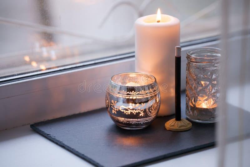 Contesto domestico di autunno di inverno, bastone di karoma e candele accoglienti e molli su un bordo di pietra sul davanzale Nat fotografie stock