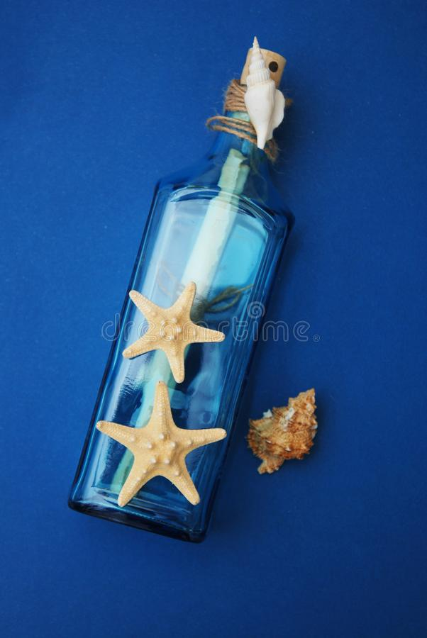 Contesto nautico di tema, bottiglia decorativa con le coperture, stelle marine sul fondo del blu di Depp Copi lo spazio Fuoco sel fotografia stock
