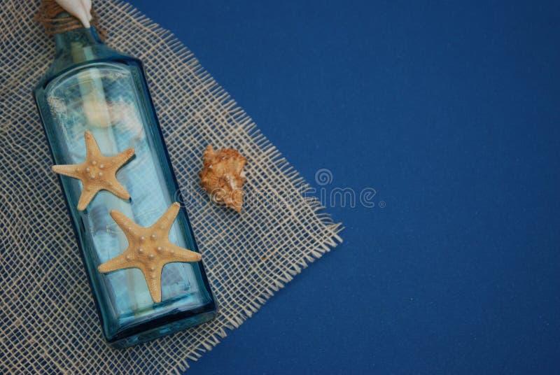 Contesto nautico di tema, bottiglia decorativa con le coperture, stelle marine sul fondo del blu di Depp Copi lo spazio Fuoco sel immagini stock
