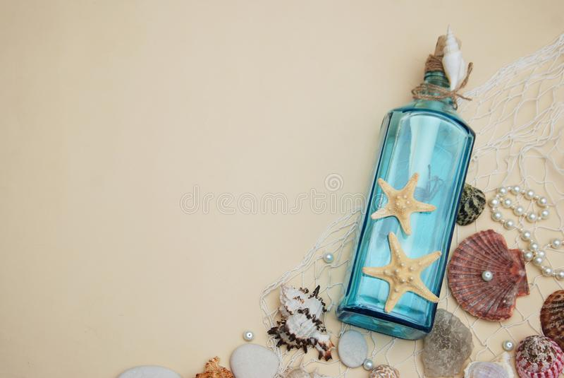 Contesto nautico di tema, bottiglia decorativa con le coperture, stelle marine sul fondo neutrale dell'avorio Posto per testo Fuo fotografia stock