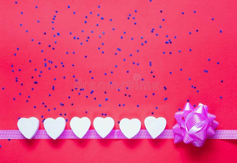 Contexto festivo Corações decorativos brancos no fundo coral com sparkles azuis fotos de stock