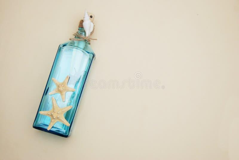 Contexto náutico del tema, botella decorativa con las cáscaras, estrellas de mar en fondo de marfil neutral Lugar para el texto F fotos de archivo