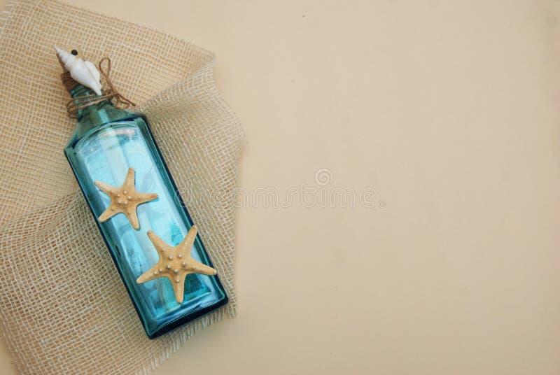 Contexto náutico del tema, botella decorativa con las cáscaras, estrellas de mar en fondo de marfil neutral Lugar para el texto F fotografía de archivo