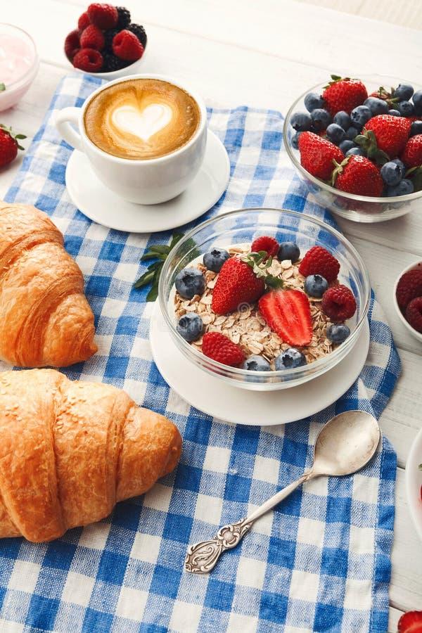 Continentaal ontbijt met croissants en bessen op geruit c stock afbeelding