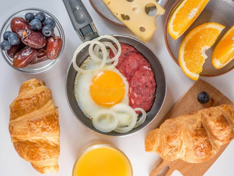 Continentaal Ontbijt met Croissants en Fried Eggs en jus d'orange en koffie en kaas op witte achtergrond stock afbeelding