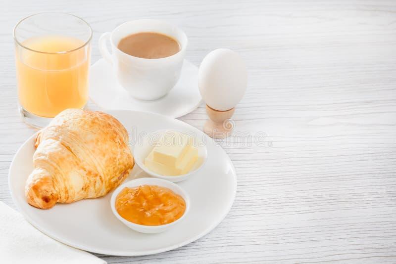 Continentaal ontbijt met een croissant, gekookt ei Koffie of thee met melk, een glas sap, broodjes, boter, jam royalty-vrije stock afbeelding