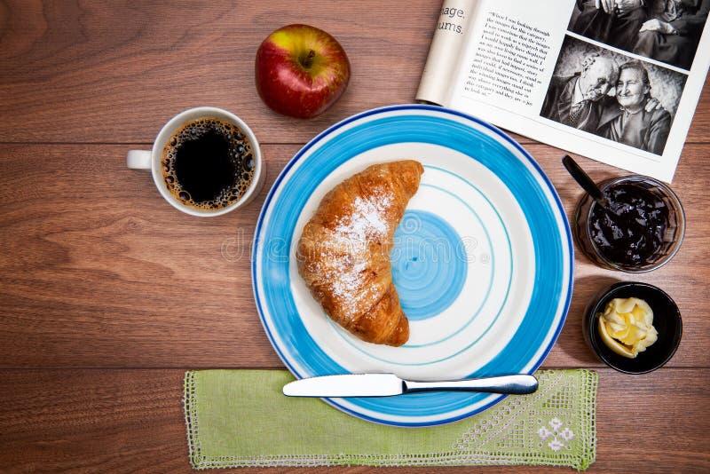Continentaal ontbijt met koffie, verse croissants, fruit en goed tijdschrift royalty-vrije stock afbeeldingen