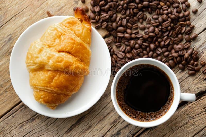 Continentaal ontbijt met vers croissant en hete koffie op houten achtergrond, decoratie met koffieboon stock foto's