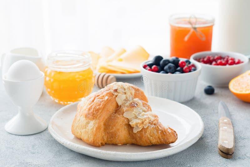 Continentaal ontbijtcroissant, honing, jam, bessen en ei royalty-vrije stock foto