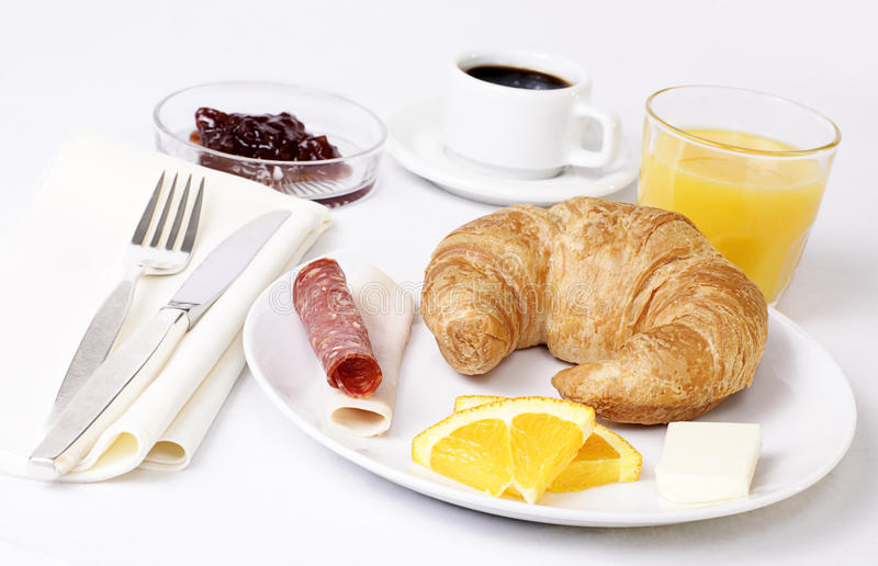 Continental breakfast. Hotel breakfast consisting of croissant, juice and coffee royalty free stock images