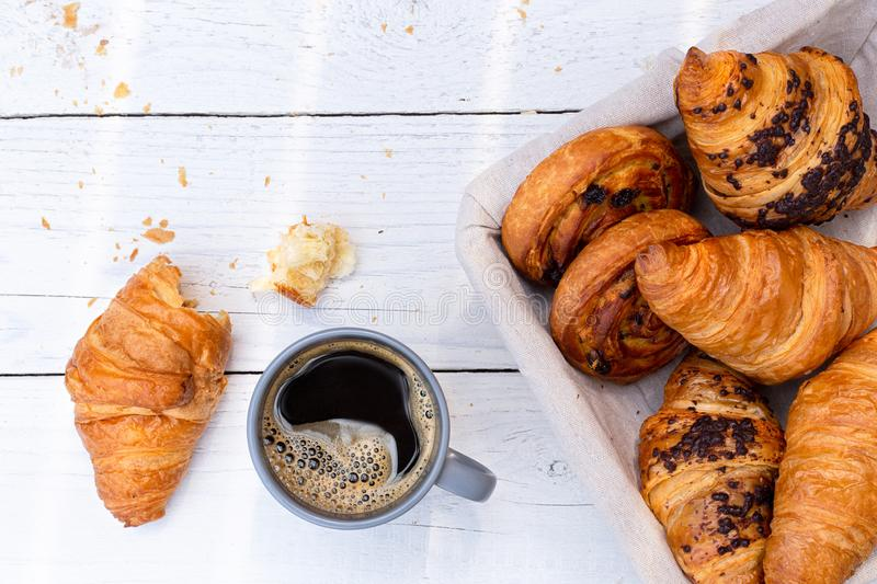 Continental breakfast with black coffee and basket of pastries. Half eaten on white wood from above.  royalty free stock images