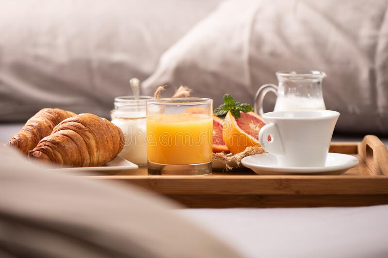 Continental breakfast. Breakfast tray on bed with coffee, orange juice and croissant stock photos